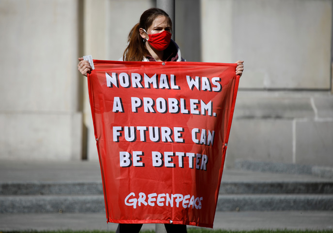 A Greenpeace protester holds a banner saying Normal was a problem. Future can be better
